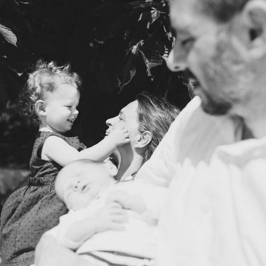 foto di famiglia in bianco e nero, mamma e figlia sul fondo a fuoco che si guardano dolcemente, in primo piano papà e figlio sfuocati. Fotografa Deborah Brugnera